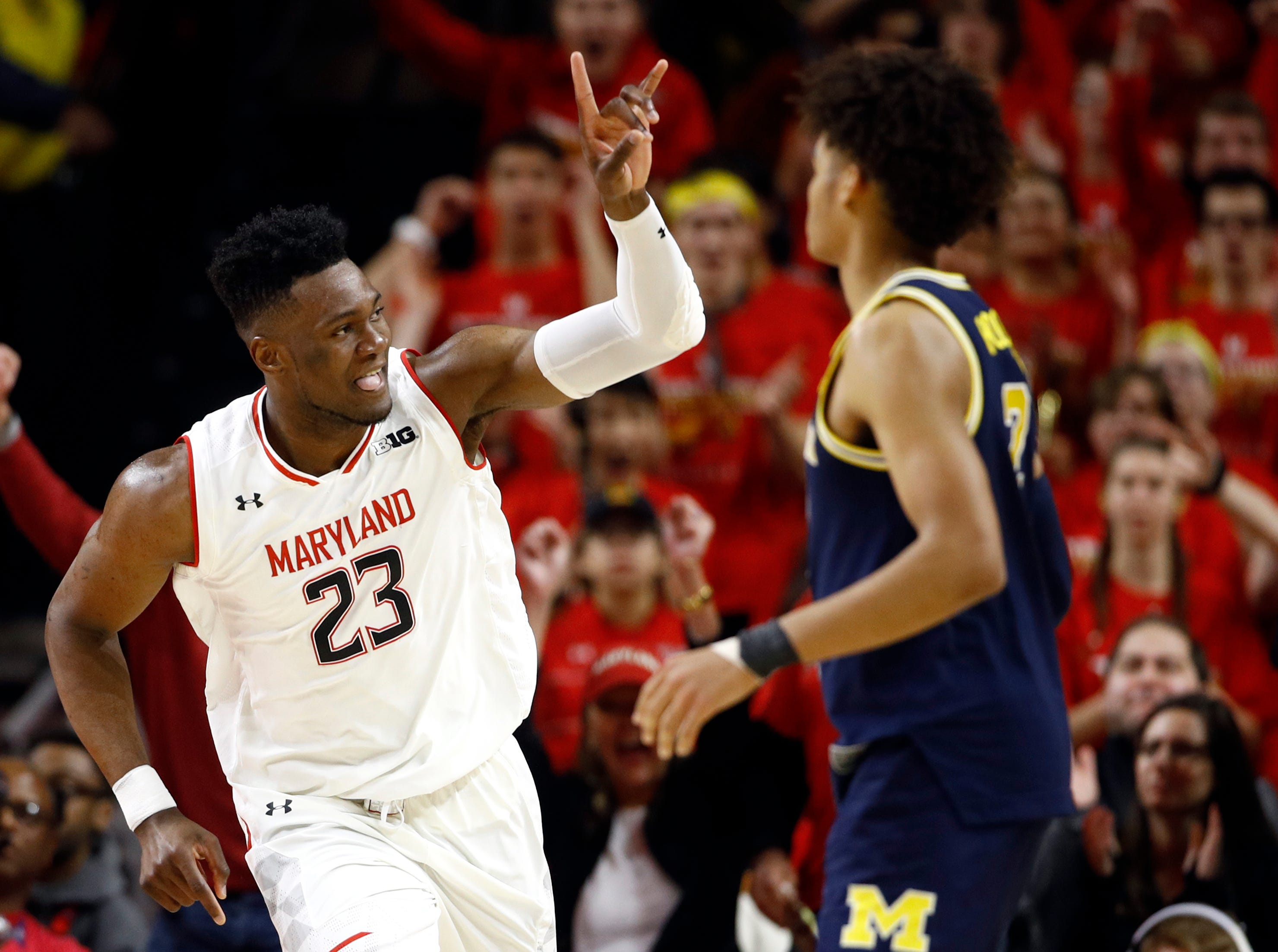 Maryland forward Bruno Fernando (23), of Angola, gestures in front of Michigan guard Jordan Poole after making a basket in the first half.
