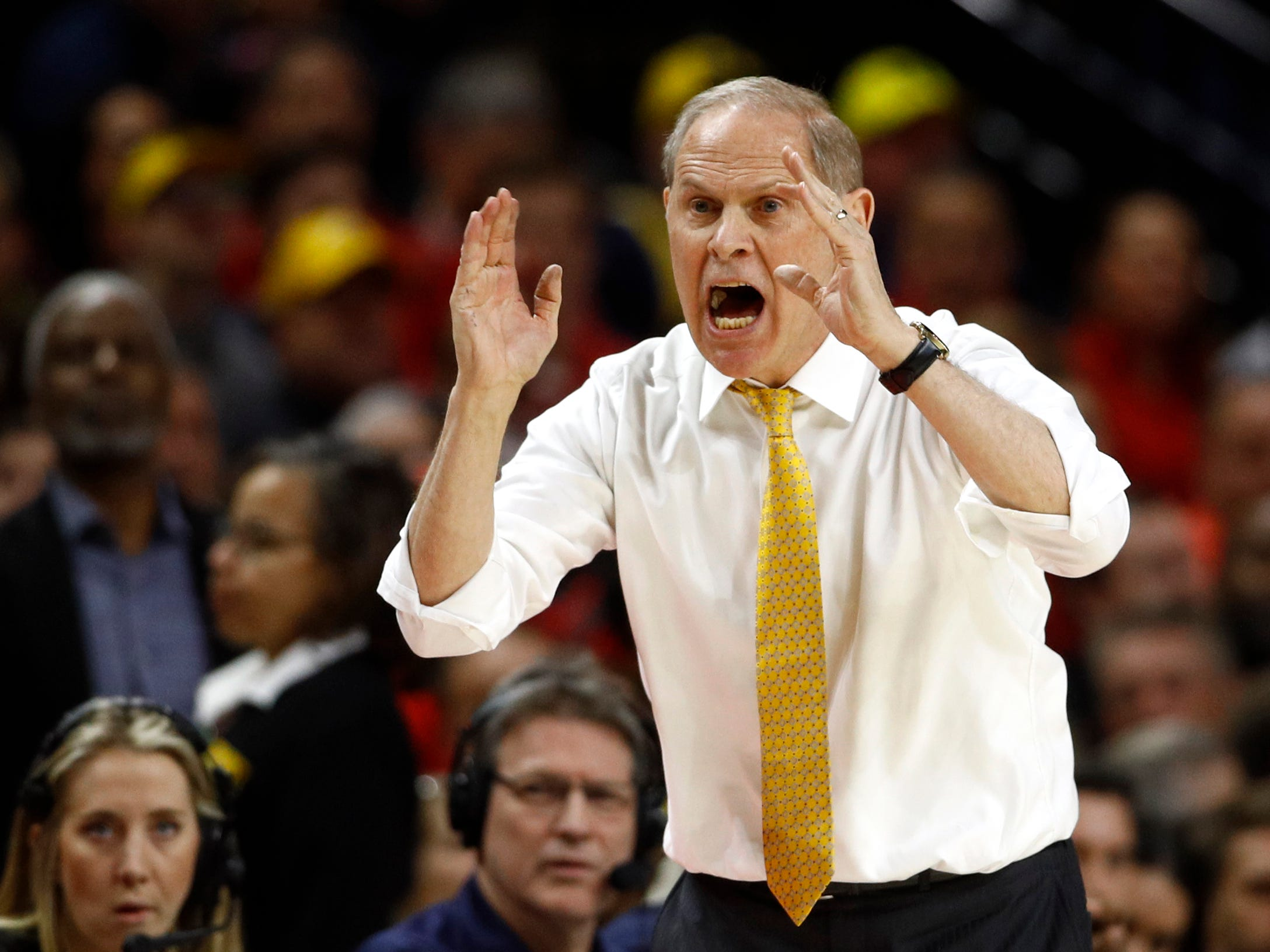 Michigan head coach John Beilein directs his players in the first half.
