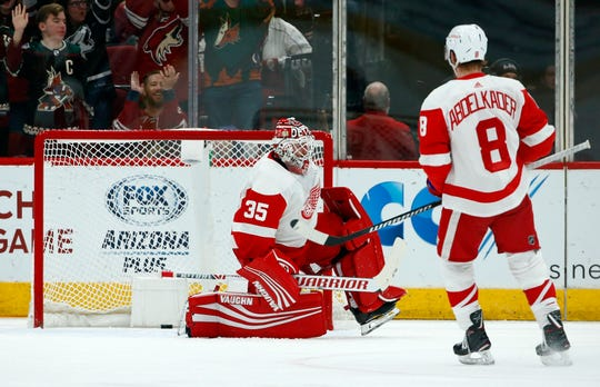 Red Wings goaltender Jimmy Howard (35) gives up a goal to Arizona Coyotes' Josh Archibald as Red Wings left wing Justin Abdelkader (8) looks on during the first period.