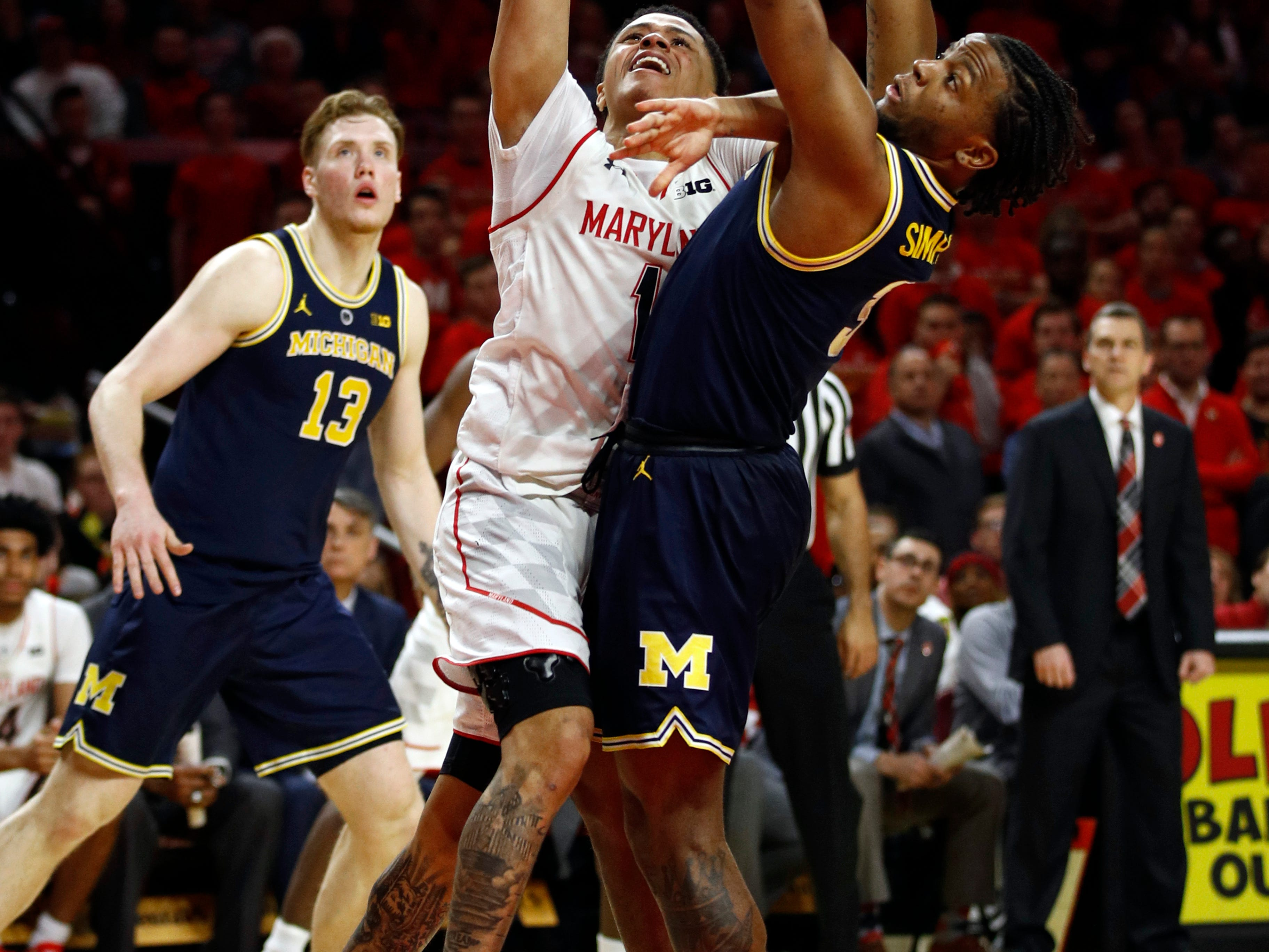 Maryland guard Anthony Cowan Jr., center, shoots between Michigan guard Zavier Simpson, right, and forward Ignas Brazdeikis, of Canada, in the second half.