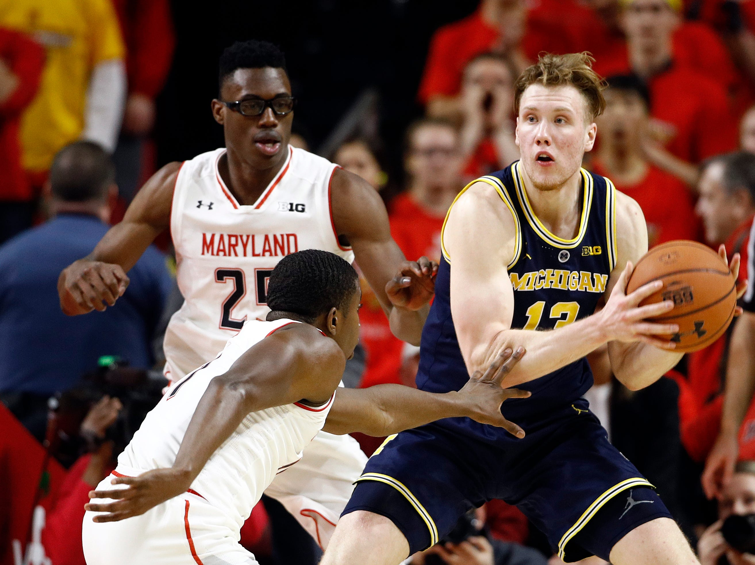 Michigan forward Ignas Brazdeikis, right, of Canada, protects the ball as he is pressured by Maryland forward Jalen Smith, left, and guard Darryl Morsell in the second half.