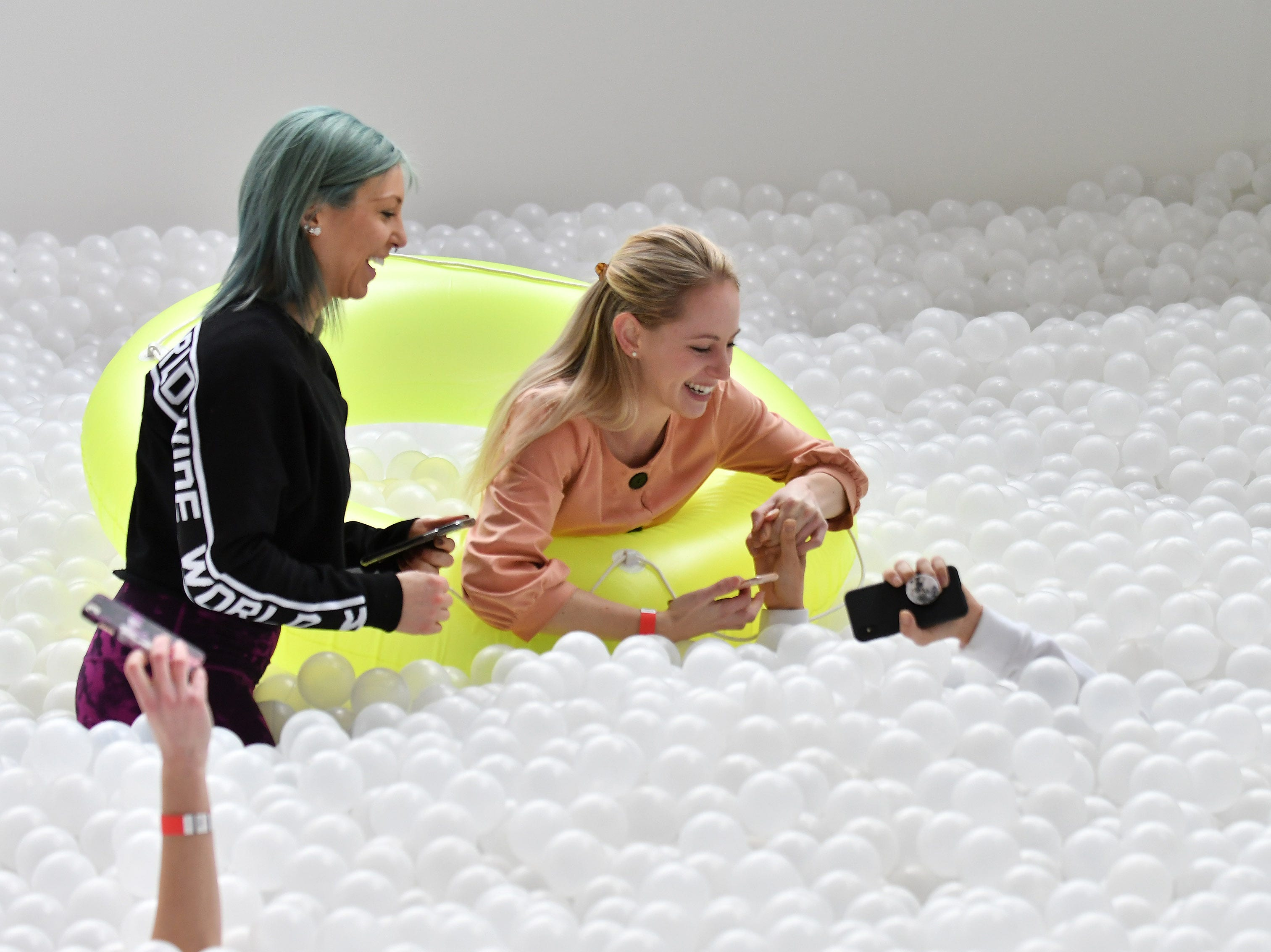 From left, Carly Kuppe, 30, of Royal Oak watches while Chelsea VanHull, 28, tries to pull up Teresa MacKinnon, 30, of Troy from beneath the surface of the balls.