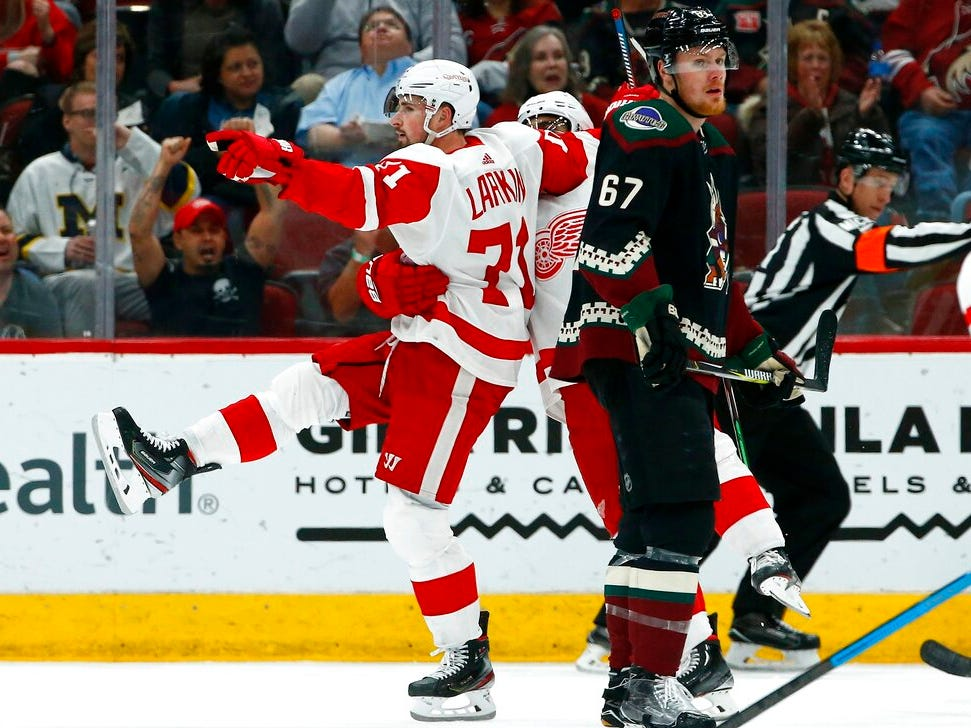 Detroit Red Wings center Dylan Larkin (71) celebrates his goal with Red Wings' Andreas Athanasiou, center, as Arizona Coyotes left wing Lawson Crouse (67) skates past during the second period.