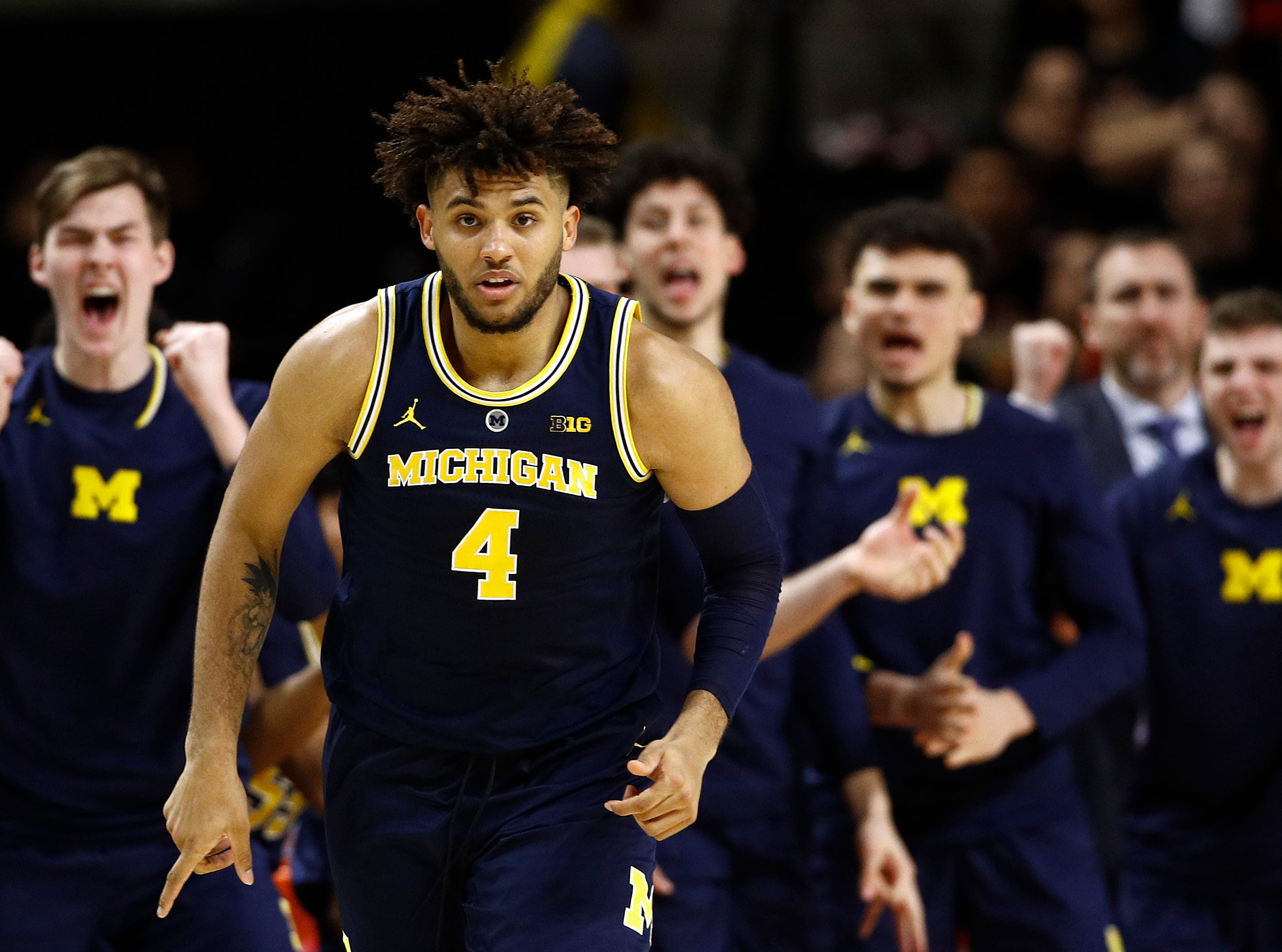 Michigan forward Isaiah Livers (4) reacts in front of teammates on the bench after making a three-point basket in the second half.