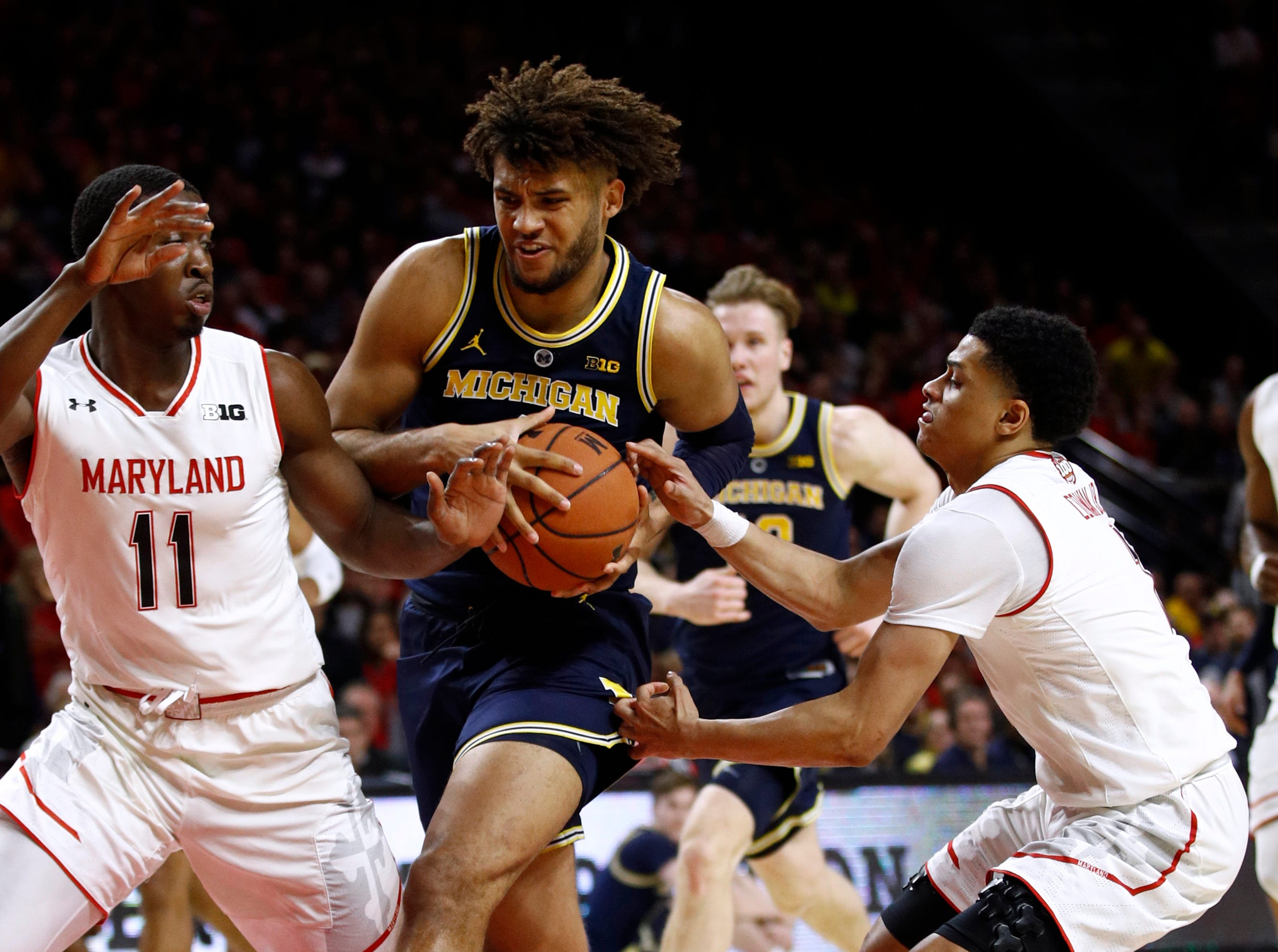Michigan forward Isaiah Livers, center, drives between Maryland guards Darryl Morsell, left, and Anthony Cowan Jr. in the first half.