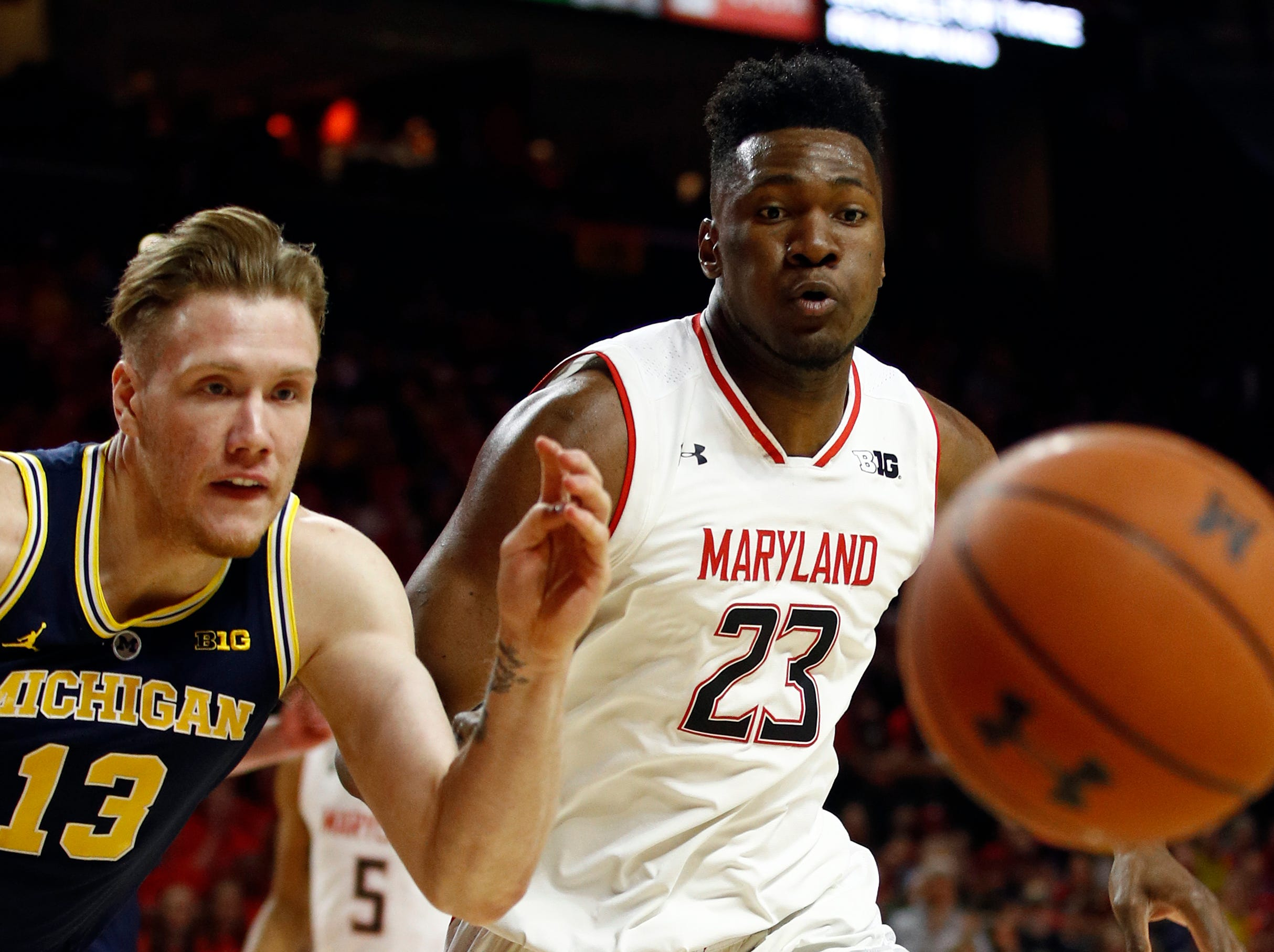 Maryland forward Bruno Fernando (23), of Angola, and Michigan forward Ignas Brazdeikis (13), of Canada, chase after the ball in the first half.