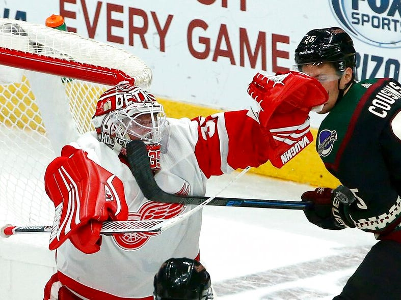 Detroit Red Wings goaltender Jimmy Howard, left, makes a save on a shot by Arizona Coyotes center Nick Cousins (25) during the third period.