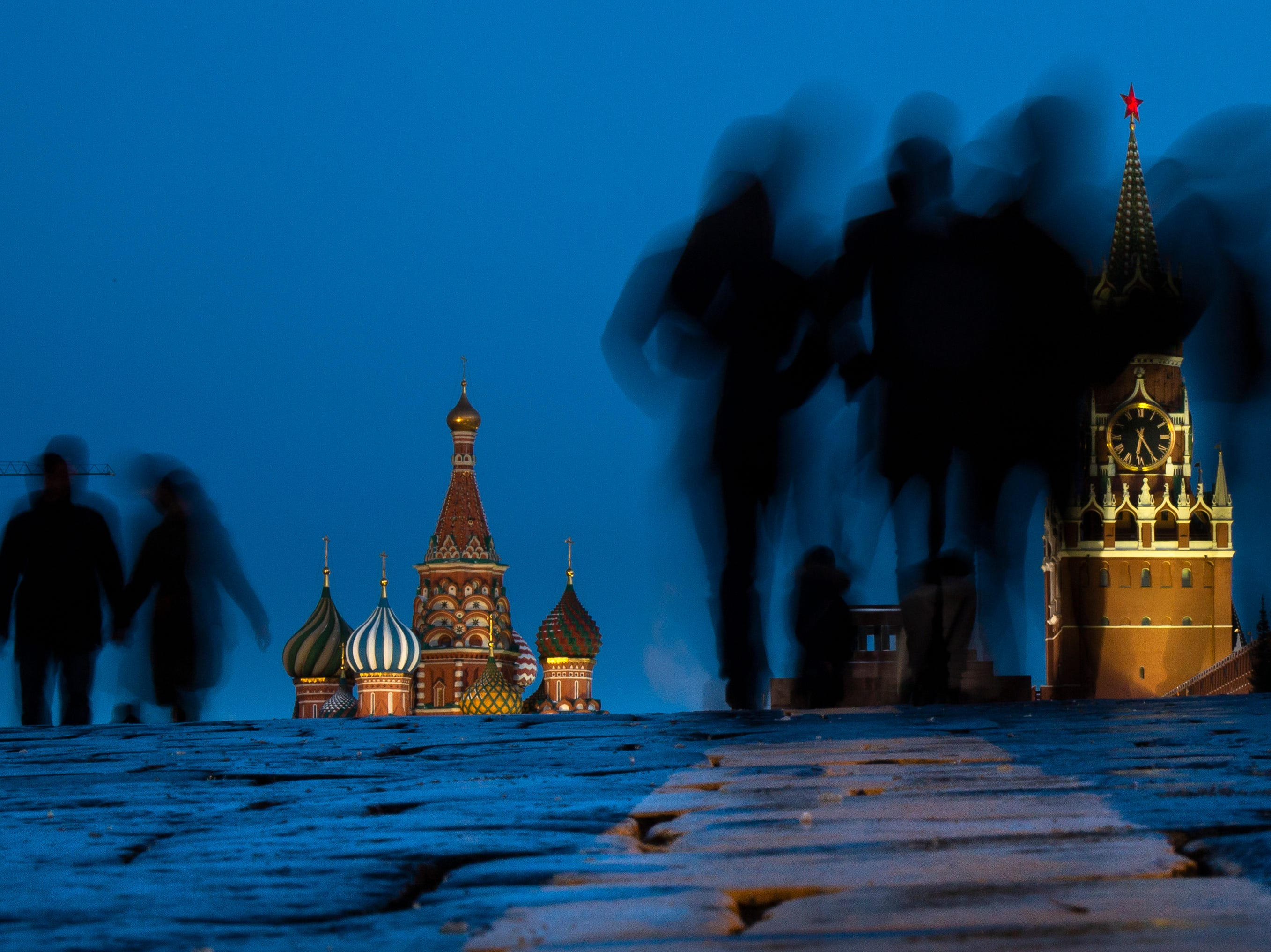 People walk through Red Square after sunset in Moscow, Russia, Sunday, March 3, 2019, with the St. Basil's background left, and the Spasskaya Tower, right, in the background.