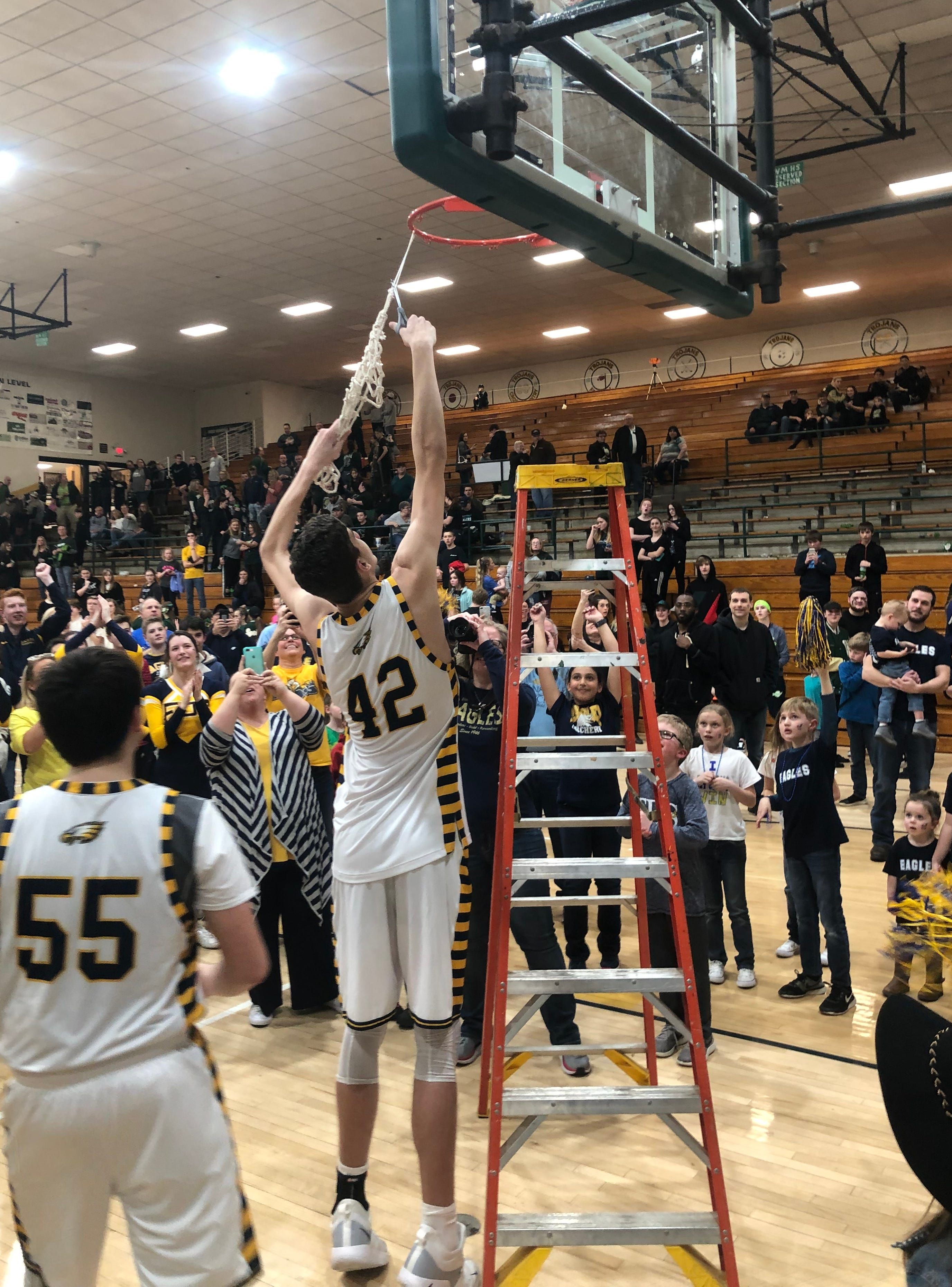 Noah Hupmann cuts a piece of the net after Day School's sectional championship win.