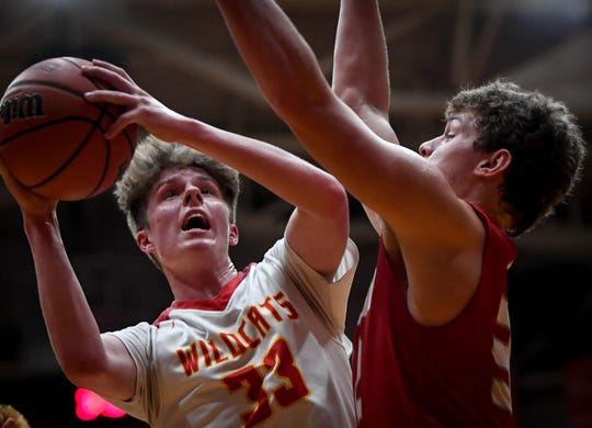 Mater Dei's Jackson Hiester (33) shoot over Braeden Beard (32) as the Mater Dei Wildcats play the Tell City Marksmen in the Class 2A Sectional Championship at Huntingburg's Memorial Gym Saturday, March 2, 2019.