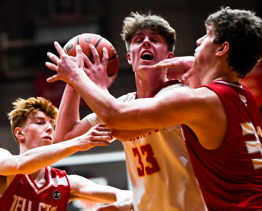 Mater Dei's Jackson Hiester (33) drives through defense from Tell City's Trent Arnold (12) and Braeden Beard (32) as the Mater Dei Wildcats play the Tell City Marksmen in the Class 2A Sectional Championship at Huntingburg's Memorial Gym Saturday, March 2, 2019.