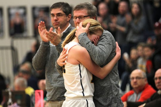 First place in sports photo category was won by Doug Hise for this photo of senior Nora LaMunyon leaving the floor for the last time to an embrace from assistant Brad Hemminger in Woodmore's district final setback.