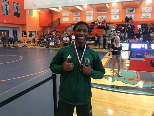 Dunbar's Ellotera Figueroa smiles as he takes third place in the 160-pound weight class in the Class 1A-Region 3 wrestling tournament Saturday.
