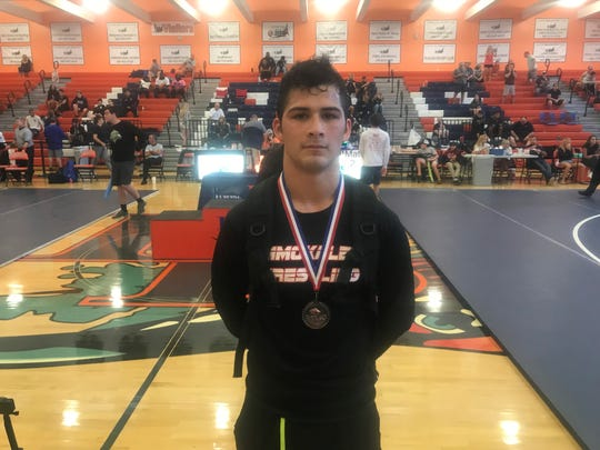 Immokalee's Nicclas Turrubiartez poses for a picture as he finishes in fourth place in the 152-pound weight class at the Class 1A-3 wrestling tournament Saturday. Turrubiartez qualifies for the state tournament in Kissimmee next week.