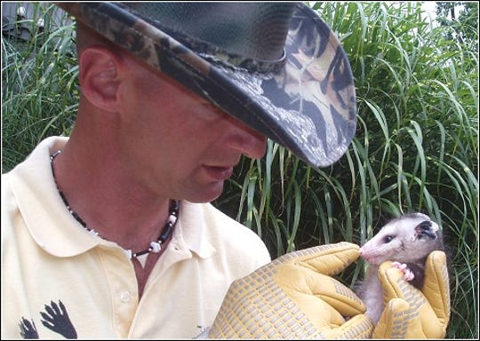 Ned Bruha of Wildlife Whisperer is shown with a opossum.