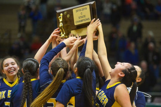 The Box Elder girls hoist the Class C state basketball championship trophy on Saturday night after defeating Roy-Winifred 48-42 in the Four Seasons Arena.