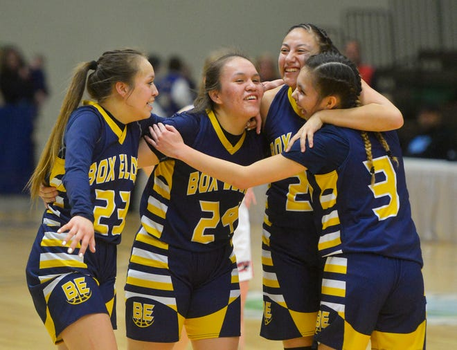 Box Elder's Kayla Momberg, 23, Joelnell Momberg, 24, Lillian Gopher, 20, and Sarah Parisian, 3, hug at center court during free throws to ice the game in the final seconds of their 48-42 victory over Roy-Winifred in the Class C state basketball championship game on Saturday night in the Four Seasons Arena.