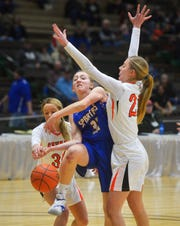 Scobey's Kortney Nelson attempts a layup as Savage's Tyler Lien and Soda Rice defend during the consolation game of the Class C Girls State Basketball Tournament on Saturday in the Four Seasons Arena.