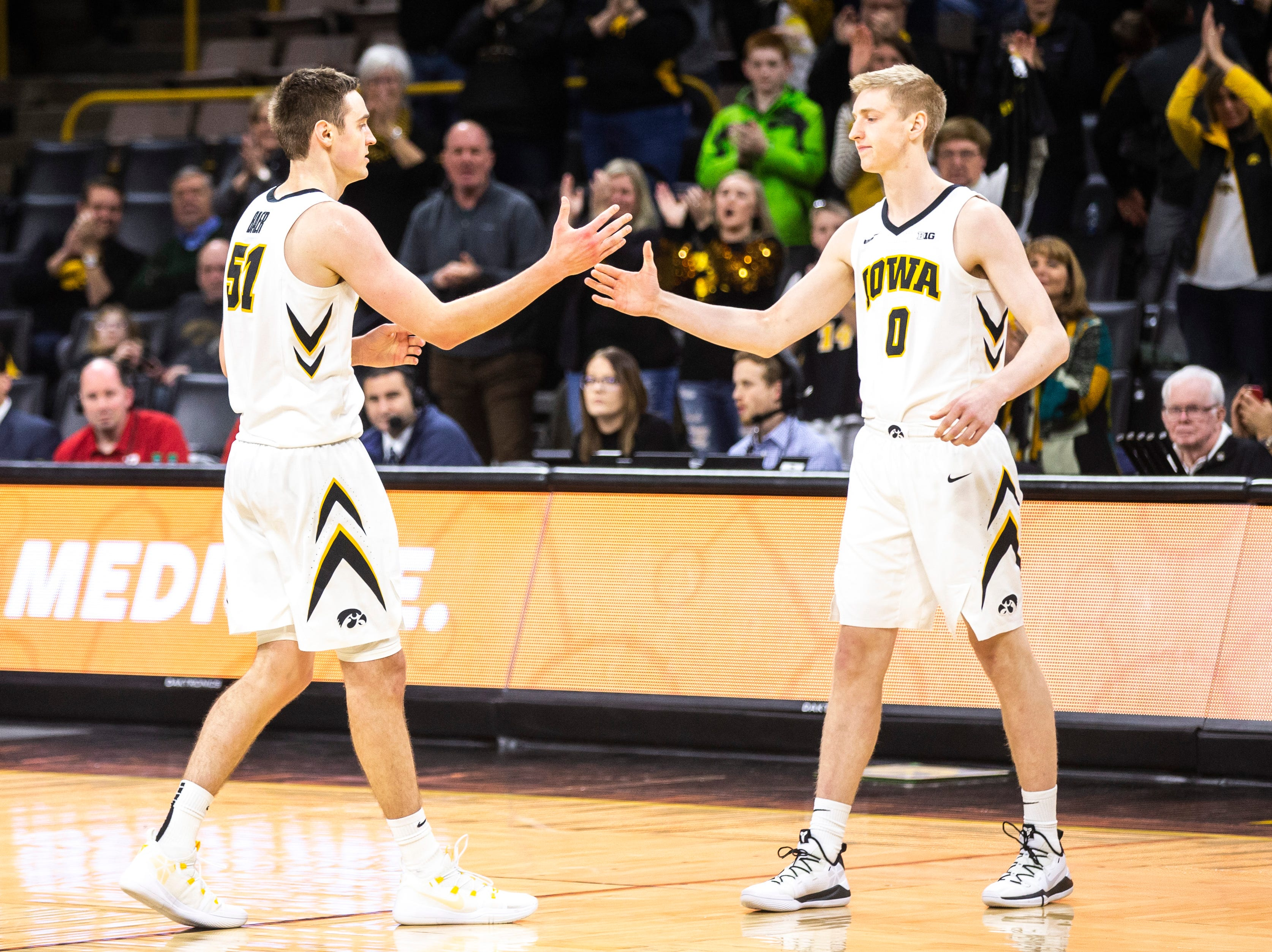 Iowa forward Nicholas Baer (51) goes to embraces his brother, Iowa forward Michael Baer (0) during a NCAA Big Ten Conference men's basketball game on Saturday, March 2, 2019, at Carver-Hawkeye Arena in Iowa City, Iowa.