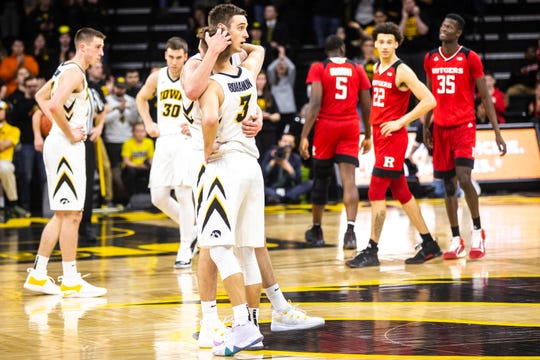 Nicholas Baer, leg, hugs close friend Jordan Bohannon (3) as he comes off the floor for the last time at Carver-Hawkeye Arena.