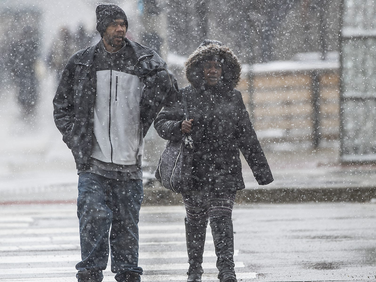 Pedestrians make their way through a bout of Sunday afternoon snow in Indianapolis on March 3, 2019. According to The Weather Channel, a chance of snow does not return until Thursday.