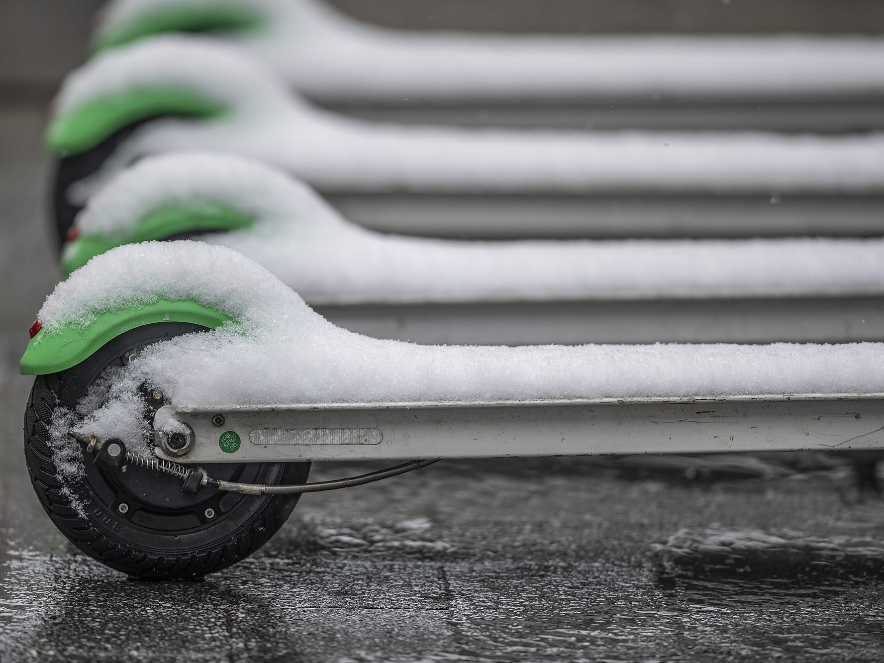 Snowfall builds up on scooters for rent during a bout of Sunday afternoon snow in Indianapolis on March 3, 2019.