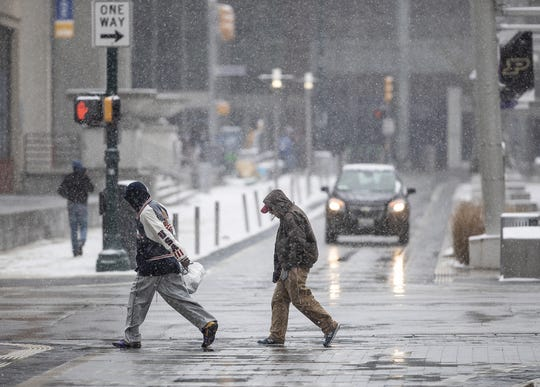 Pedestrians make their way through a bout of Sunday afternoon snow in Indianapolis on March 3, 2019.