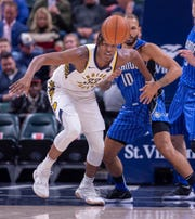 Indiana Pacers center Myles Turner (33) watches as the ball flies out of his control while being defended by Orlando Magic guard Evan Fournier (10) during the first half of an NBA basketball game, Saturday, March 2, 2019, in Indianapolis.