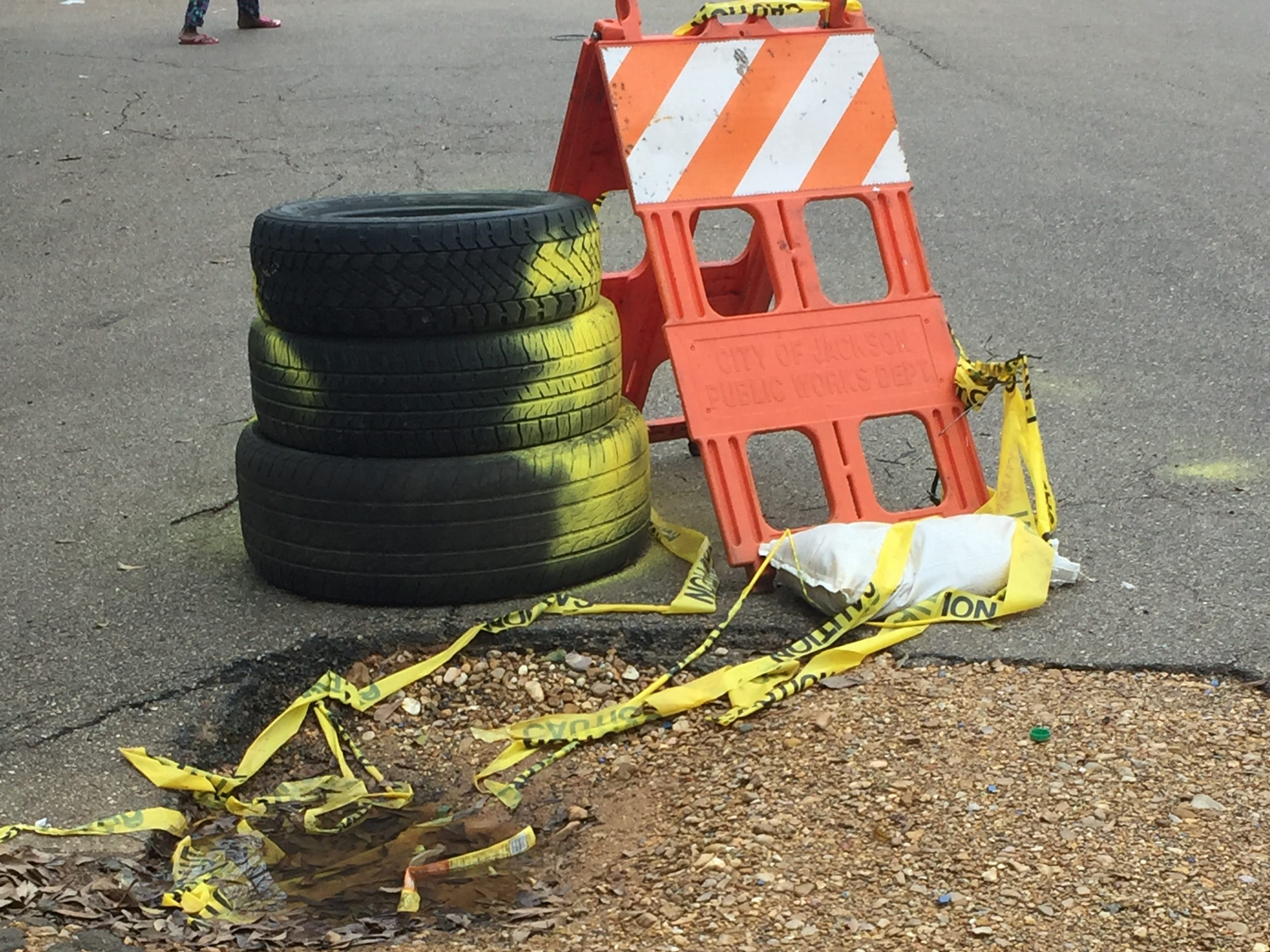 Tires painted by residents, along with a city barricade, mark pothole problems on Mitchell Street in Jackson's Fondren neighborhood on Saturday, March 2, 2019.