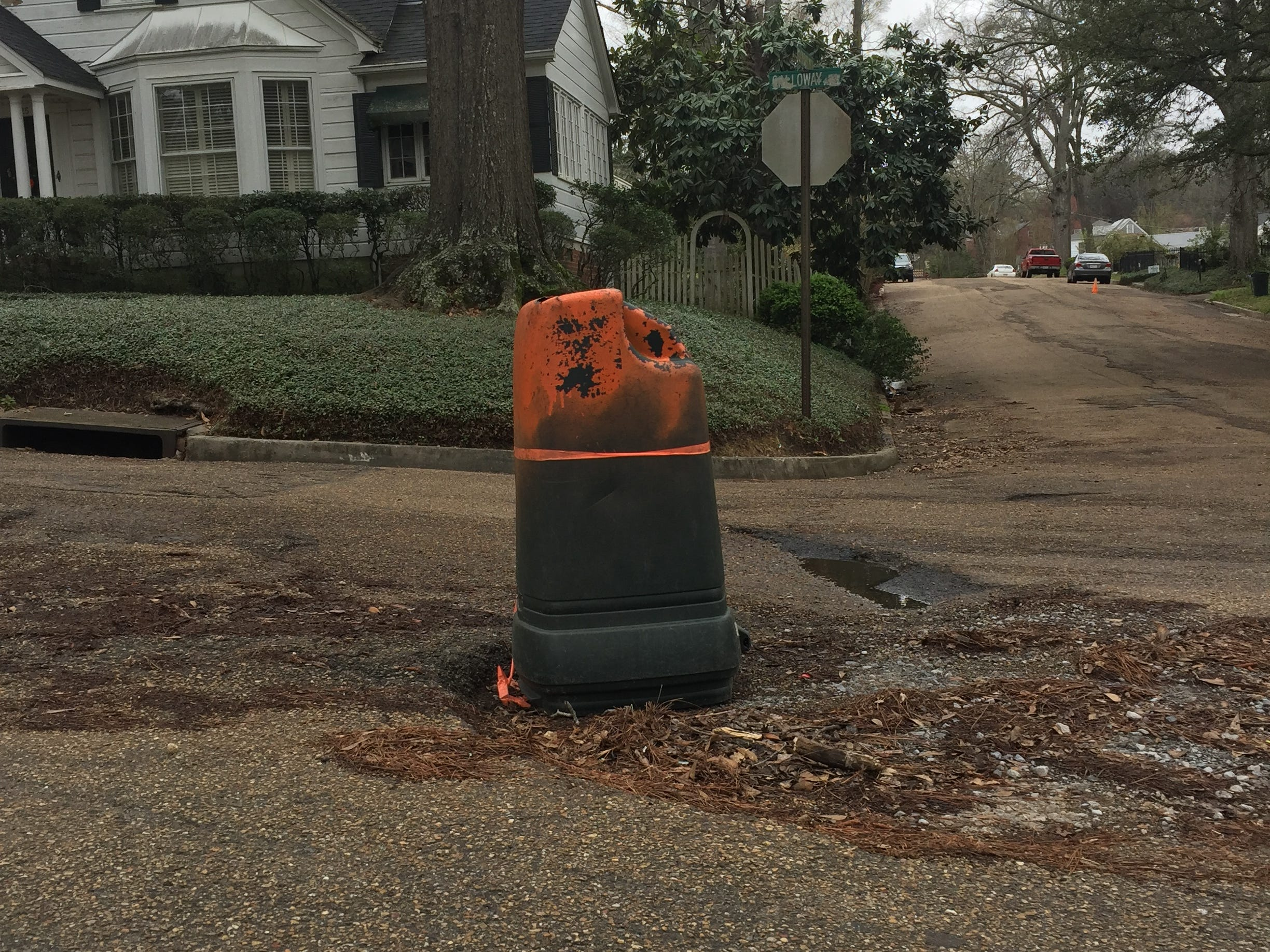 A resident has spray-painted the top of a garbage can to warn drivers of potholes on Broadway at Galloway in Jackson's Fondren neighborhood, Saturday, March 2, 2019.