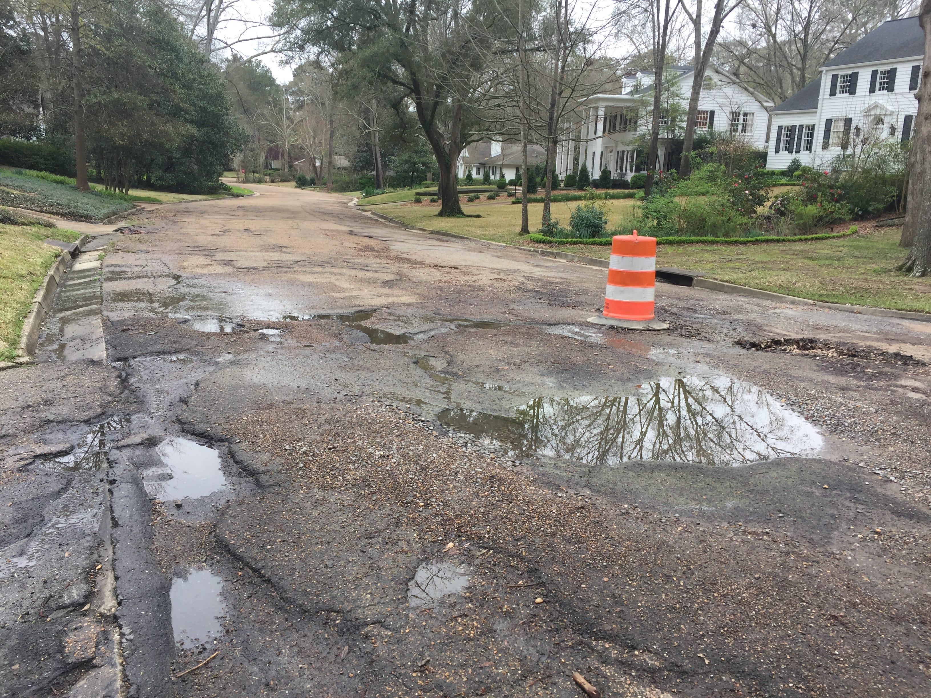 Well-kept homes on Avondale in Jackson's Fondren neighborhood are separated by a street riddled with potholes and in need of repair Saturday, March 2, 2019.