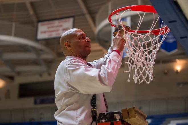 West Lafayette coach David Wood cuts down the net last March after the Red Devils won a third straight sectional title.