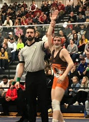 Mansfield Senior's Josh Lyons has his hand raised in victory after he won by first period pin in his third-place match at the Division II district tournament in Norwalk.