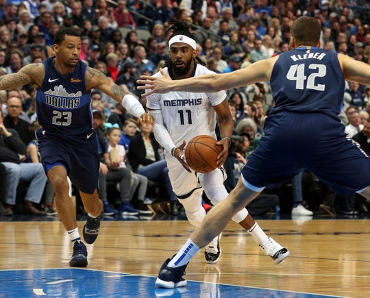 Memphis Grizzlies guard Mike Conley (11) tries to drive the ball between Dallas Mavericks guard Trey Burke (23) and forward Maximilian Kleber (42) in the second quarter of an NBA basketball game Saturday, March 2, 2019, in Dallas. (AP Photo/Richard W. Rodriguez)