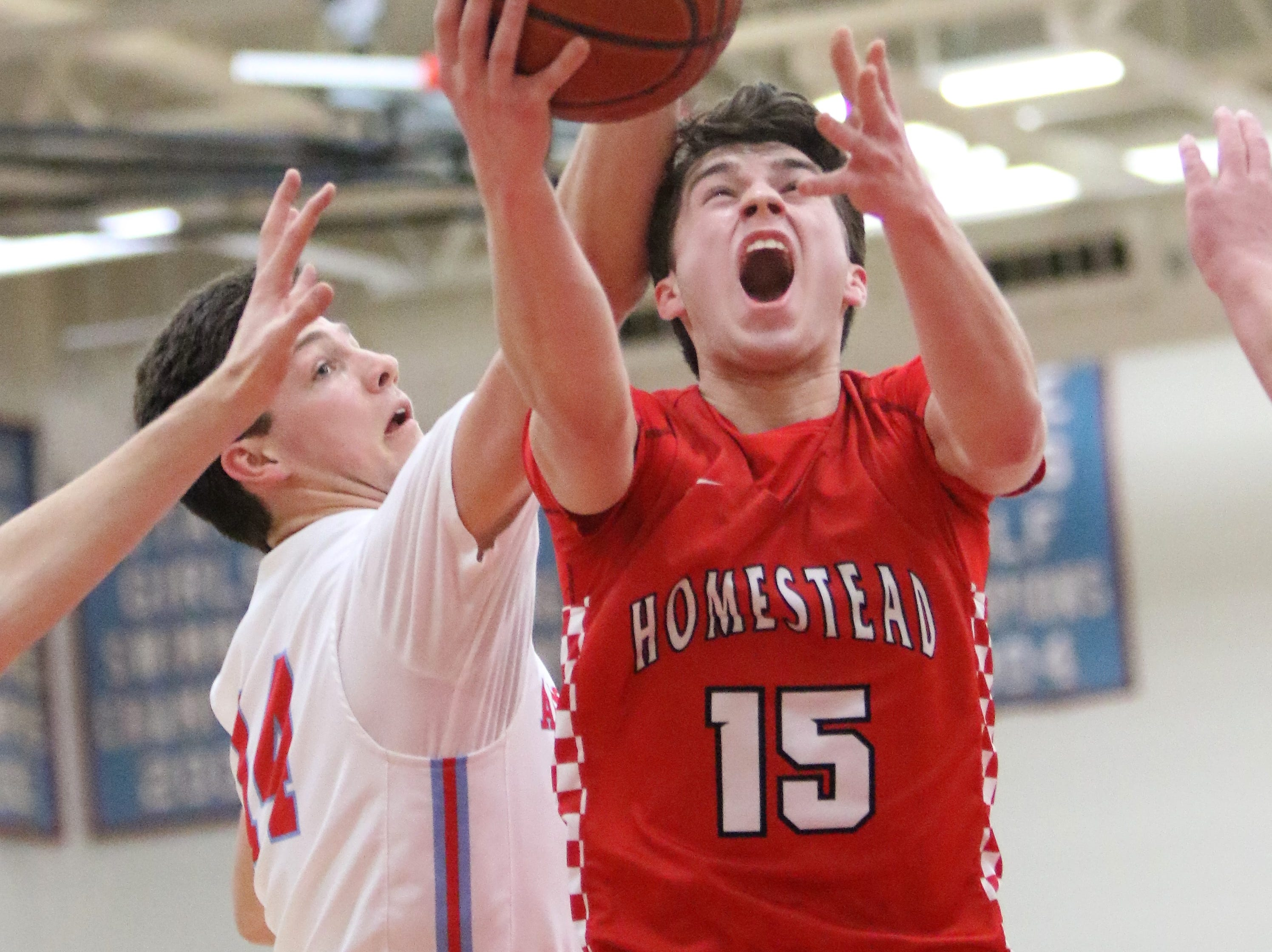 Homestead guard Ryan Waddell slices past Arrowhead forward Carter Gilmore for two points during a regional final on March 2, 2019.