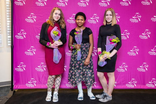 Lyrique Jackson (center) poses for a photo during a Girls on the Run fundraiser. The running club provides opportunities for girls to socialize with each other and work with coaching mentors.