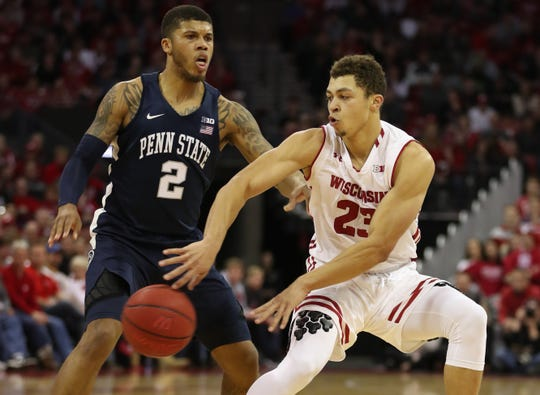 Badgers guard Kobe King drops a bounce pass around Penn State guard Myles Dread.