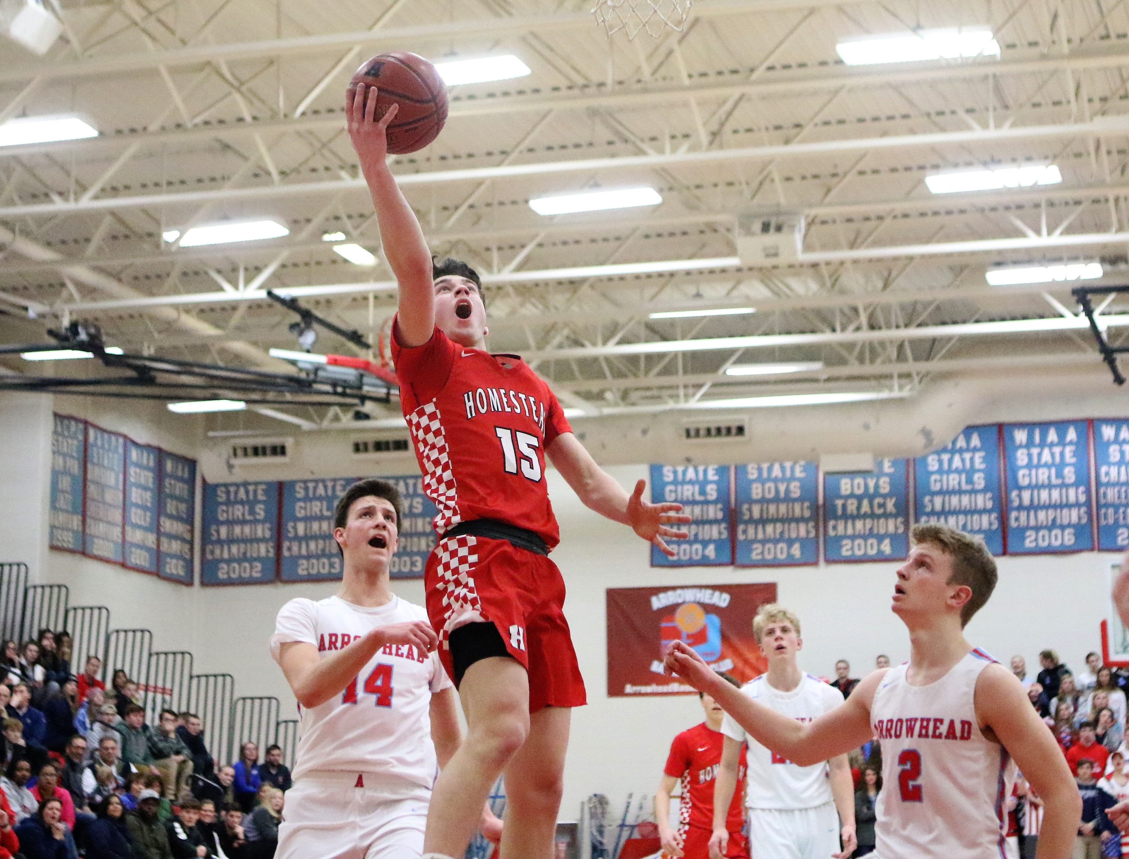 Homestead guard Ryan Waddell goes up for a layup as Arrowhead defenders watch during a WIAA regional final on March 2, 2019.