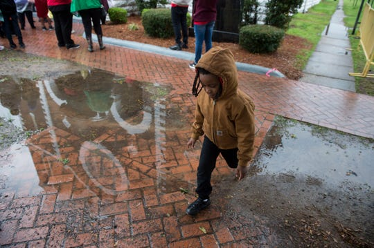 Jaziah Vaughn, 6, of Huntsville skips over a puddle outside Brown Chapel A.M.E. Church in Selma, Ala., on Sunday, March 3, 2019.