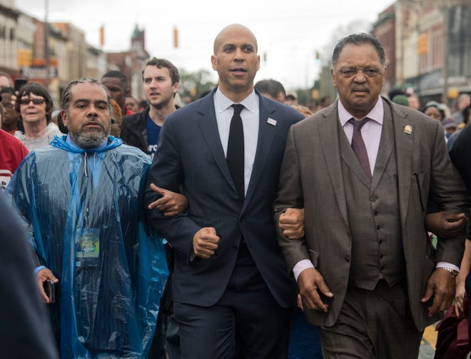 Sen. Cory Booker, middle, and Rev. Jesse Jackson, right, march in downtown Selma, Ala., on Sunday, March 3, 2019.