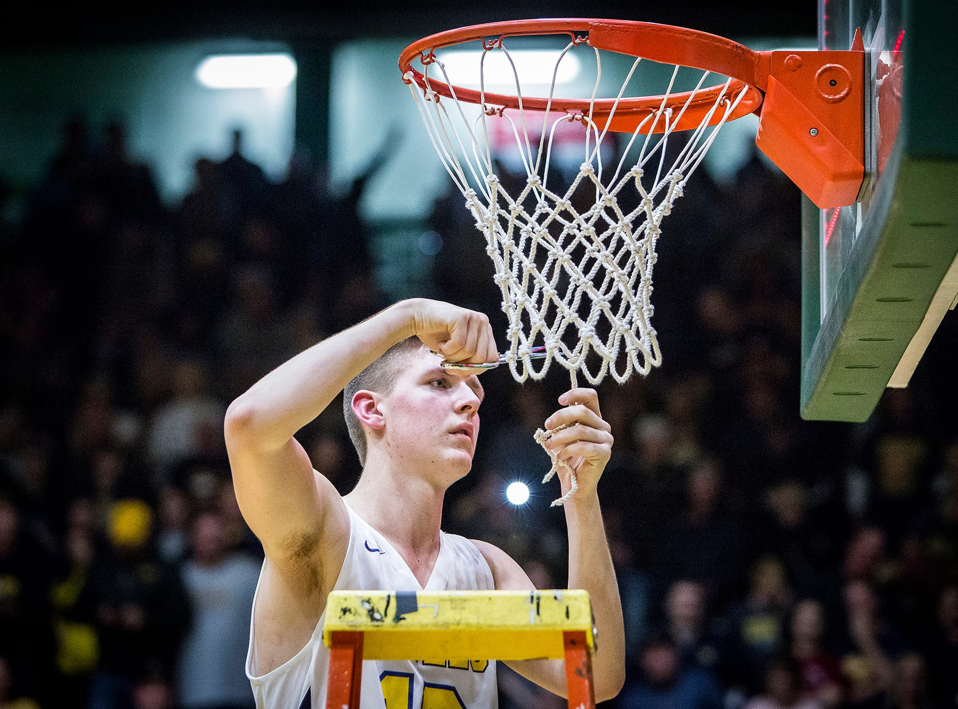 Delta's Tyler Wilburn takes his turn cutting the net after the Eagles defeated New Castle 59-55 to win the sectional championship March 2, 2019.