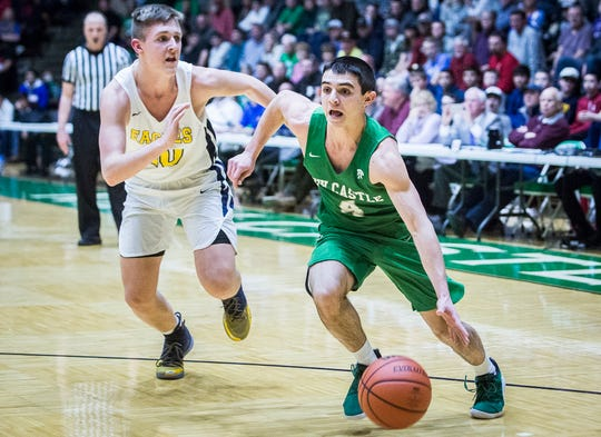 FILE -- New Castle's Cole McDaniel dribbles past Delta in their sectional championship game at New Castle High School Saturday, March 2, 2019. McDaniel scored 20 points in the Trojans 2019-20 opener after averaging 3.3 points per game last season.