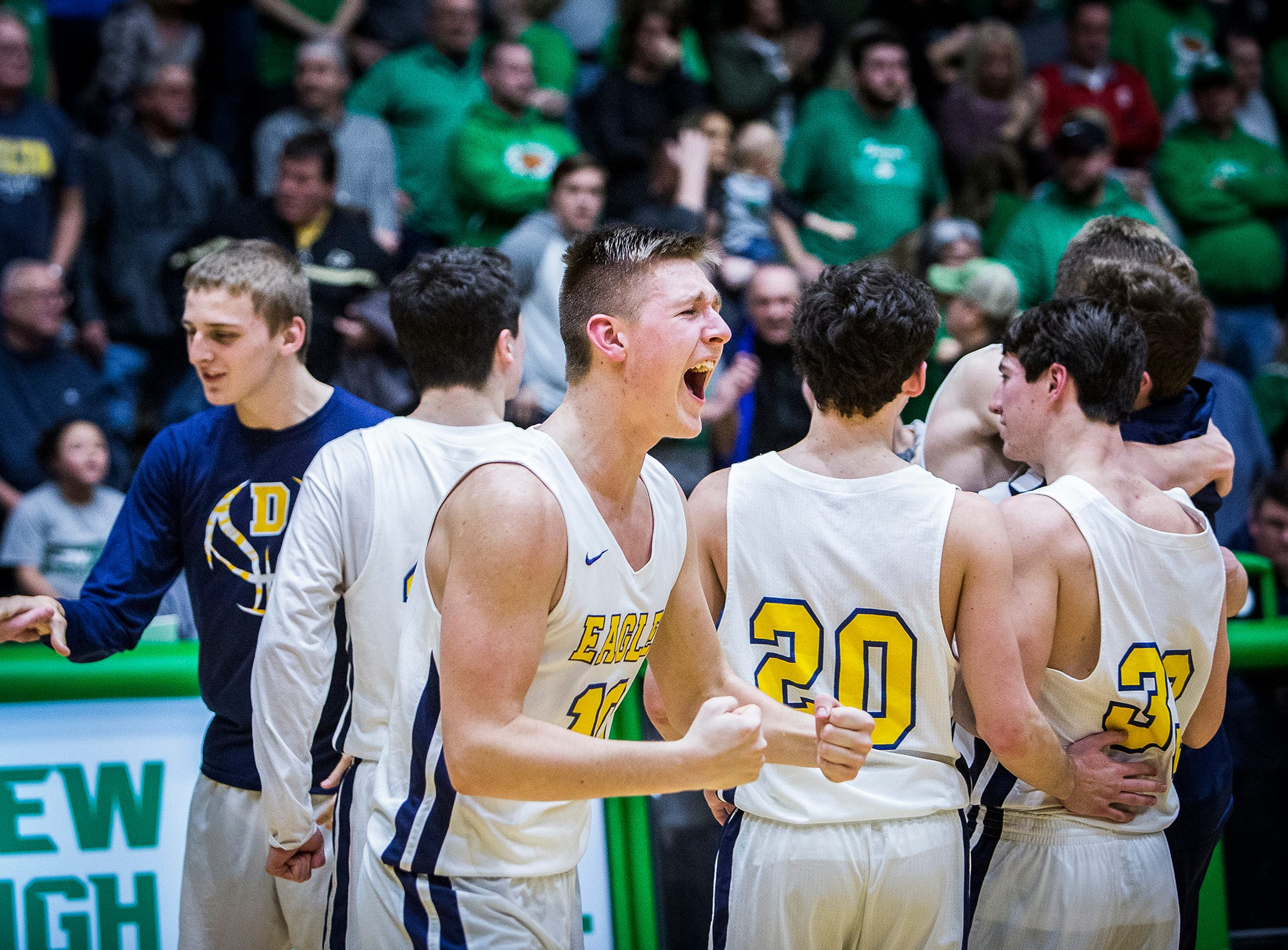 Delta's Tyler Wilburn reacts after the Eagles defeated New Castle 59-55 to win their first sectional title since 2011.