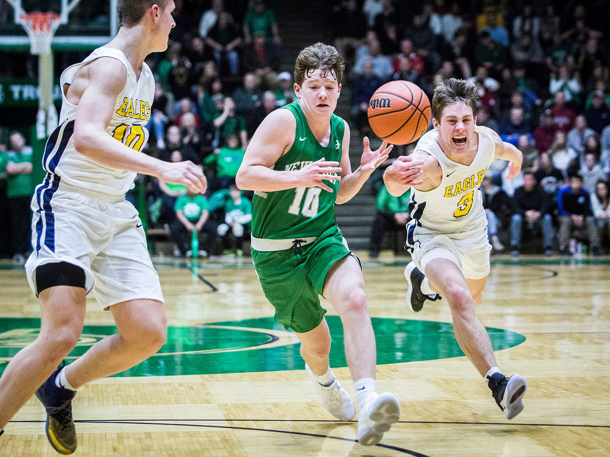 New Castle's Mason Hardwick drives against Delta's Zach Garner, right, and Tyler Wilburn during their sectional championship game at New Castle High School Saturday, March 2, 2019.