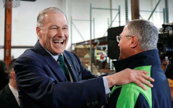Washington Gov. Jay Inslee, left, greets his brother, Frank Inslee, right, Friday, March 1, 2019, following a campaign event at A&R Solar in Seattle. Jay Inslee announced that he will seek the 2020 Democratic presidential nomination, mixing calls for combating climate change and highlights of his liberal record with an aggressive critique of President Donald Trump.