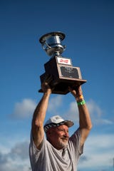 Dan Greenling holds up his first place trophy during the Swamp Buggy Races at Florida Sports Park in Naples on Sunday, March 3, 2019.
