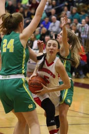 Fairfield Christian's Hope Custer attempts to slip between Newark Catholic's Shannon Keck and Brynn Peddicord during Saturday's Division IV district final at New Albany. The Green Wave won 68-56.
