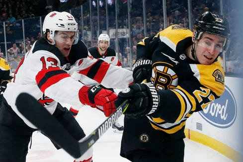 Boston Bruins' John Moore (27) and New Jersey Devils' Nico Hischier (13) battle along the boards during the first period of an NHL hockey game in Boston, Saturday, March 2, 2019.