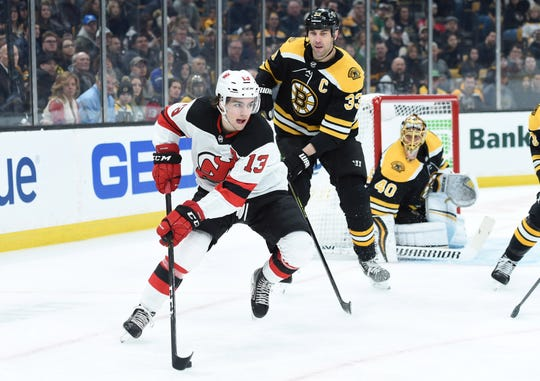 Mar 2, 2019; Boston, MA, USA; New Jersey Devils center Nico Hischier (13) controls the puck in front of Boston Bruins defenseman Zdeno Chara (33) during the first period at TD Garden.