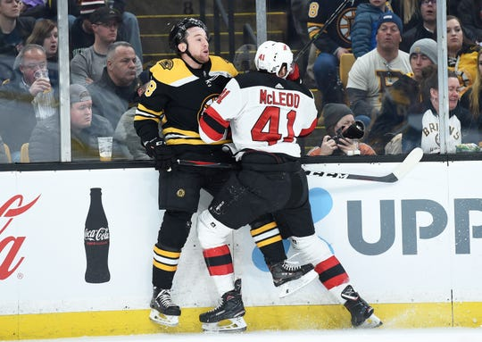 Mar 2, 2019; Boston, MA, USA; New Jersey Devils center Michael McLeod (41) checks Boston Bruins defenseman Matt Grzelcyk (48) into the boards during the first period at TD Garden.